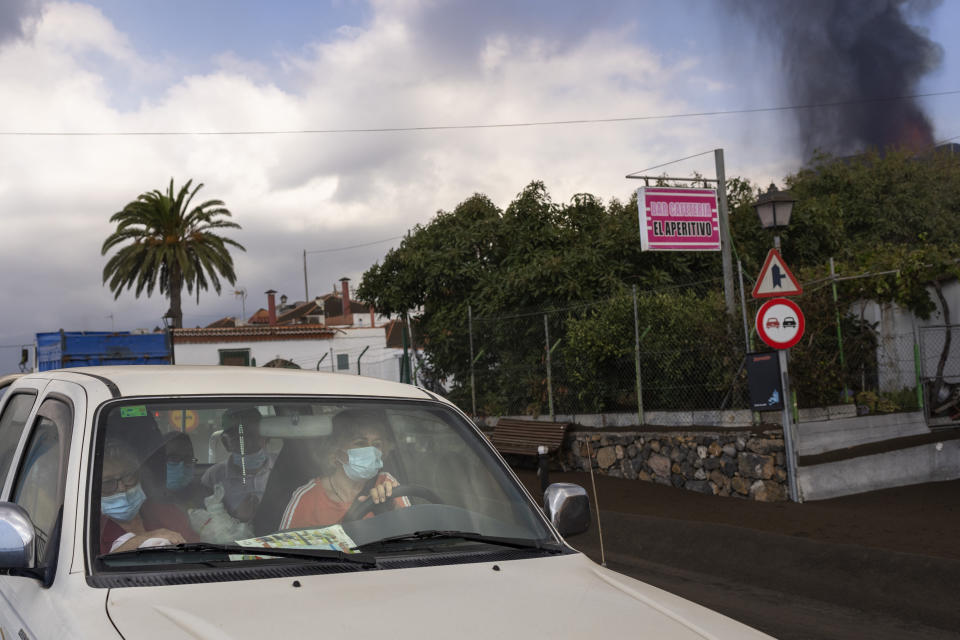 Residents leave their house as lava continues to flow from an erupted volcano, in La Mancha on the island of La Palma in the Canaries, Spain, Friday, Sept. 24, 2021. A volcano in Spain's Canary Islands continues to produce explosions and spew out lava, five days after it erupted. Two rivers of lava continue to slide slowly down the hillside of La Palma on Friday. (AP Photo/Emilio Morenatti)