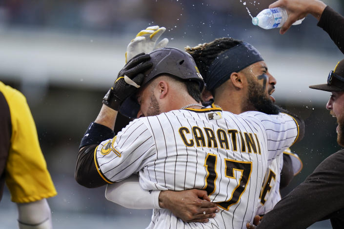 San Diego Padres' Victor Caratini (17) celebrates with Fernando Tatis Jr., second from right, and teammates after reaching on an RBI-single to defeat the San Francisco Giants in a baseball game Thursday, Sept. 23, 2021, in San Diego. (AP Photo/Gregory Bull)