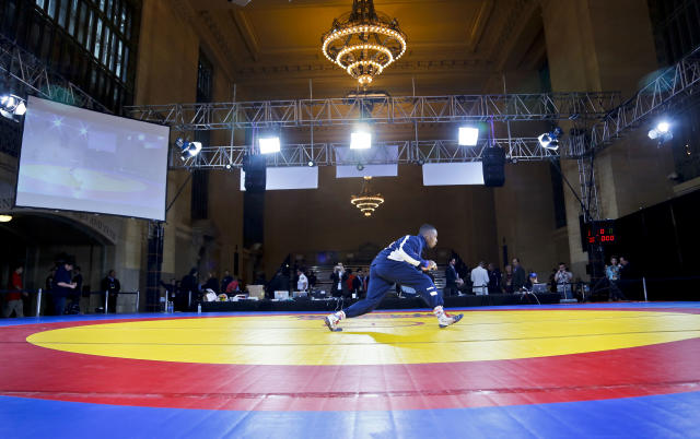 """U.S. freestyle wrestler Obe Blanc warms up for an exhibition wrestling match at Grand Central Terminal, Wednesday, May 15, 2013, in New York. """"The Rumble on the Rails"""" exhibition, featuring teams from the USA, Iran and Russia, raises money for charity but is also aimed at drawing attention to the sport's attempt to stay in the Olympics. (AP Photo/Bebeto Matthews)"""