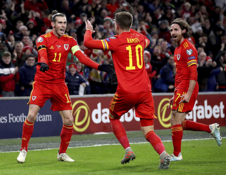 Wales' Aaron Ramsey celebrates scoring his side's first goal of the game against Hungary, with team-mates Gareth Bale, left, and Joe Allen, right, during  their UEFA Euro 2020 Qualifying soccer match at the Cardiff City Stadium, in Cardiff, Wales, Tuesday Nov. 19, 2019. (Nick Potts/PA via AP)