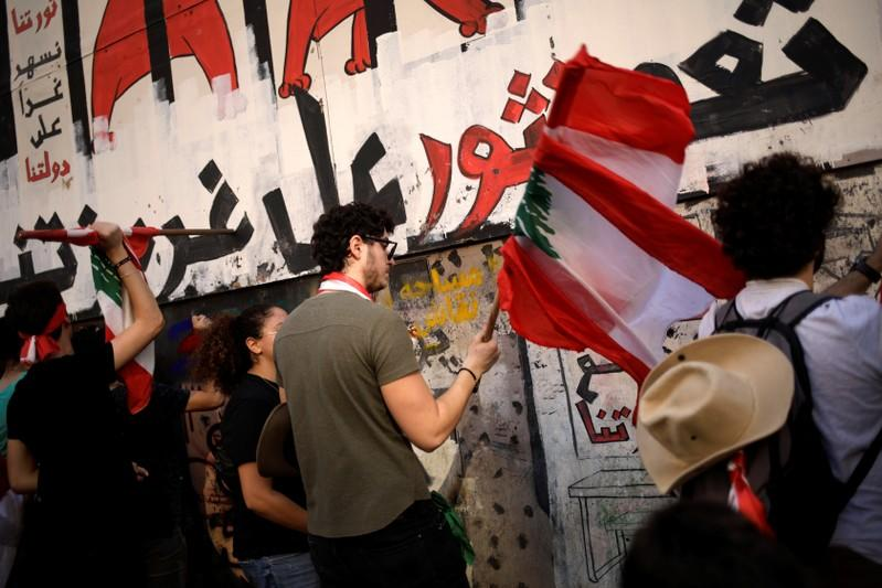 Protesters hit the fencing of a wrecked building at a demonstration organised by students during ongoing anti-government protests in Beirut