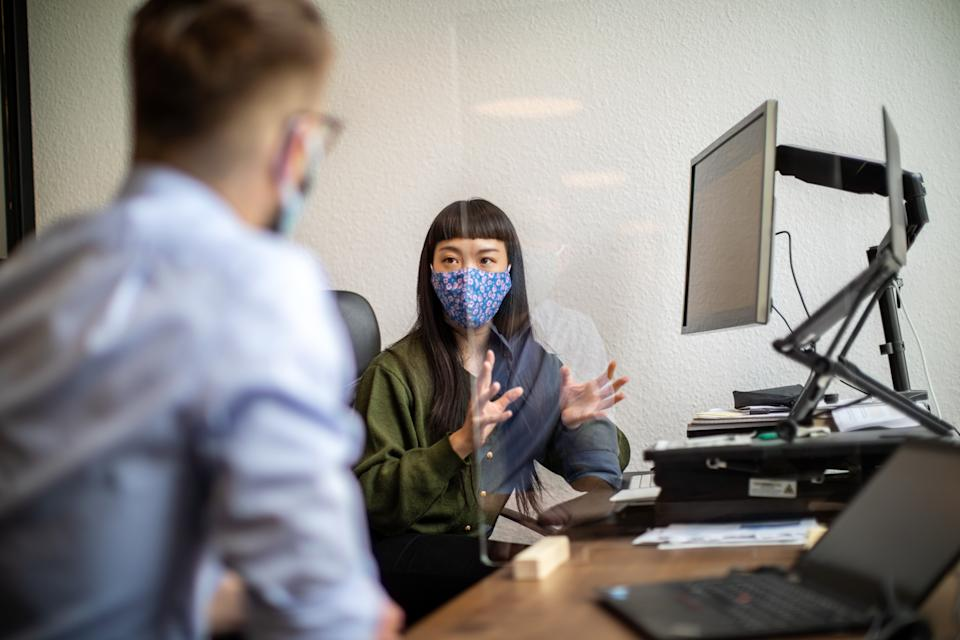 Businesswoman discussing work through glass partition with colleague at office desk. Business people back to work sitting at desk with protection guard between them post covid-19 pandemic.