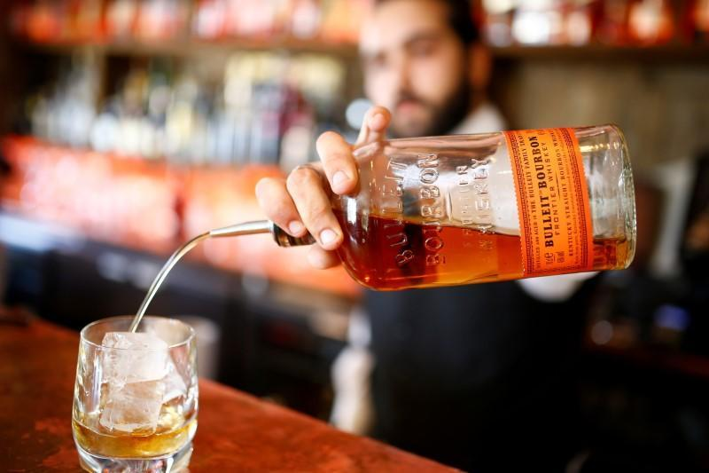 FILE PHOTO: A barman poses as he pours a glass of Bourbon whiskey at the World's End pub in London