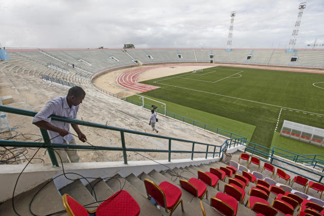 A man runs cables prior to the reopening of the soccer stadium in Mogadishu, Somalia Tuesday, June 30, 2020. At least three mortar blasts struck the Mogadishu Stadium Tuesday evening, just hours after it was reopened by Somalia's President Mohamed Abdullahi Mohamed, who had left before the shells hit, following years of instability. (AP Photo/Farah Abdi Warsameh)