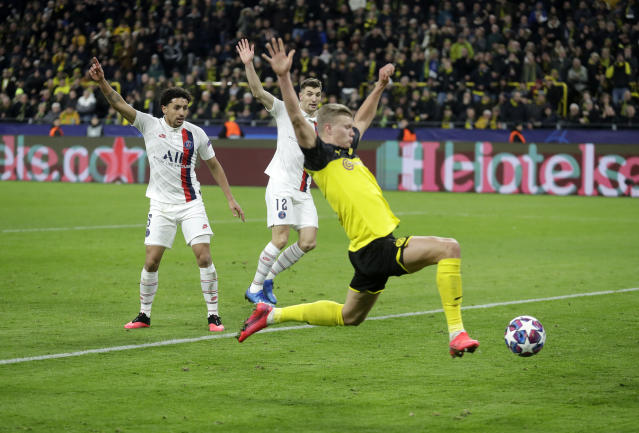 Dortmund's Erling Braut Haaland, front, scores his side's opening goal during the Champions League round of 16 first leg soccer match between Borussia Dortmund and Paris Saint Germain in Dortmund, Germany, Tuesday, Feb. 18, 2020. (AP Photo/Michael Probst)