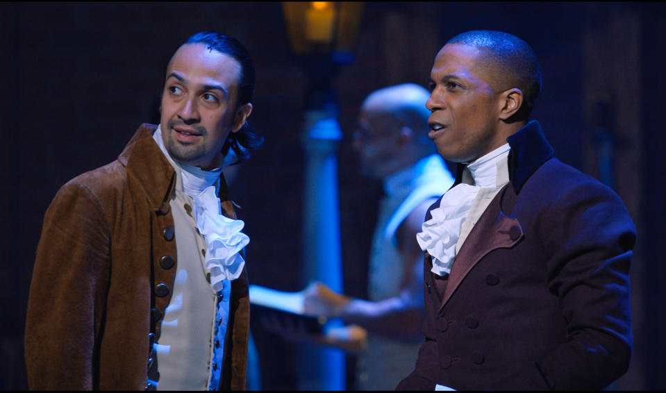 """This image released by Disney+ shows Lin-Manuel Miranda, left, and Leslie Odom Jr. during a performance of """"Hamilton."""" Miranda was nominated for a Golden Globe for best actor in a motion picture musical or comedy on Wednesday, Feb. 3, 2021 for his role in the film. (Disney+ via AP)"""