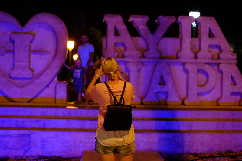 "Tourist pose for photo at a sculpture that read ""I Love Ayia Napa"" in the southeast resort of Ayia Napa in the easter Mediterranean island of Cyprus late Wednesday, July 17, 2019. A Cyprus police official says 12 Israelis have been detained after a 19-year-old British woman alleged that she was raped in the resort town of Ayia Napa. (AP Photo/Petros Karadjias)"
