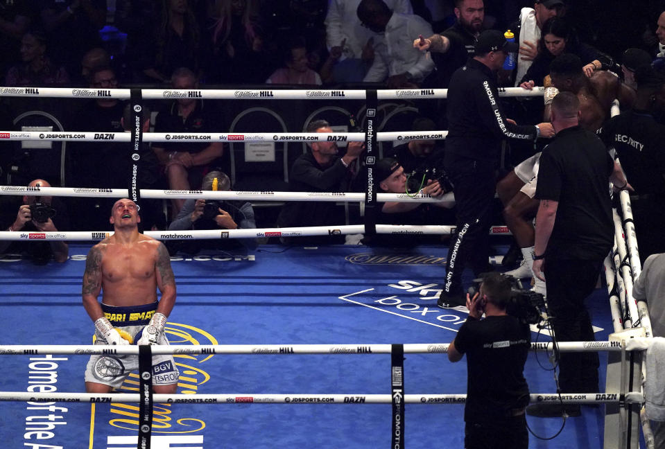 Oleksandr Usyk, left, of Ukraine celebrates after winning the WBA (Super), WBO and IBF boxing title bout against Anthony Joshua, right, of Britain at the Tottenham Hotspur Stadium in London Saturday Sept. 25, 2021. (Nick Potts/PA via AP)