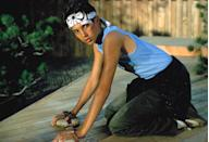 <ul> <li><strong>What to wear:</strong> A blue graphic tank top with blank pants and the iconic white headband.</li> </ul>