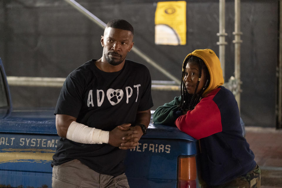 "This image released by Netflix shows Jamie Foxx, left, and Dominique Fishback in a scene from ""Project Power."" The film, streaming Friday, imagines a world where a pill can give temporary superpowers. (Skip Bolen/Netflix via AP)"