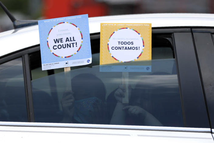 FILE - In this June 25, 2020, file photo, two young children hold signs through the car window that make reference to the 2020 U.S. Census as they wait in the car with their family at an outreach event in Dallas. A delay in census data is scrambling plans in some states to redraw districts for the U.S. House and state legislatures. The Census Bureau has said redistricting data that was supposed to be provided to states by the end of March won't be ready until August or September. (AP Photo/Tony Gutierrez, File)