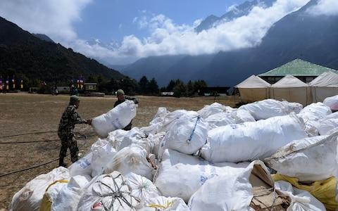 Nepali Army personnel collect waste from Mount Everest at Namche Bazar in Solukhumbu district - Credit: AFP