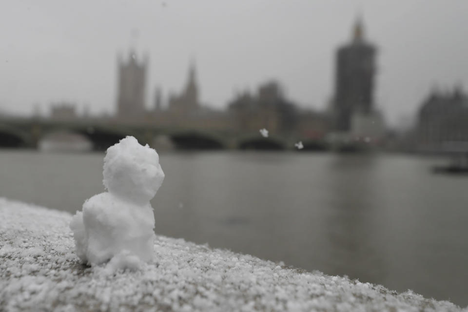 A little snowman sits on the embankment opposite parliament as temperatures dropped below freezing during the third coronavirus lockdown in London, Tuesday, Feb. 9, 2021. (AP Photo/Kirsty Wigglesworth)