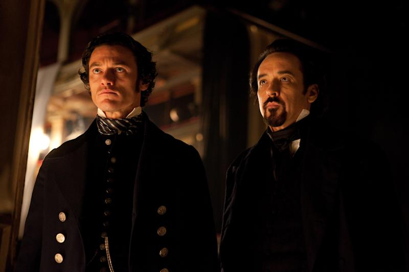 """In this film publicity image released by Relativity Media, Luke Evans portrays Detective Fields , left, and John Cusack portrays Edgar Allan Poe in a scene from the gothic thriller """"The Raven."""" (AP Photo/Relativity Media, Larry Horricks)"""