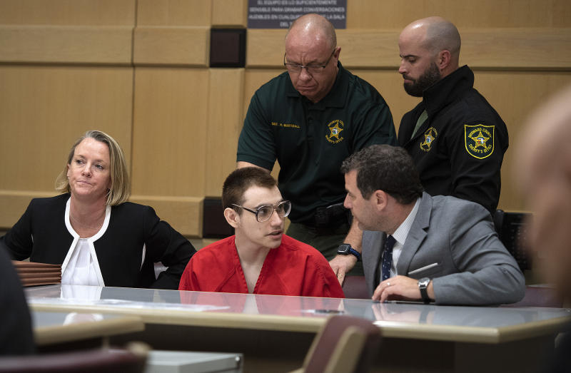 Florida school shooting defendant Nikolas Cruz speaks with attorney Gabe Ermine in Judge Elizabeth Scherer's courtroom at the Broward County Courthouse, Thursday, Dec. 19, 2019, in Fort Lauderdale, Fla. The trial of Parkland school shooting defendant Nikolas Cruz was delayed Thursday until at least next summer, when he will face a death penalty case stemming from the February 2018 massacre that left 17 people dead. (Michael Laughlin/South Florida Sun-Sentinel via AP, Pool)