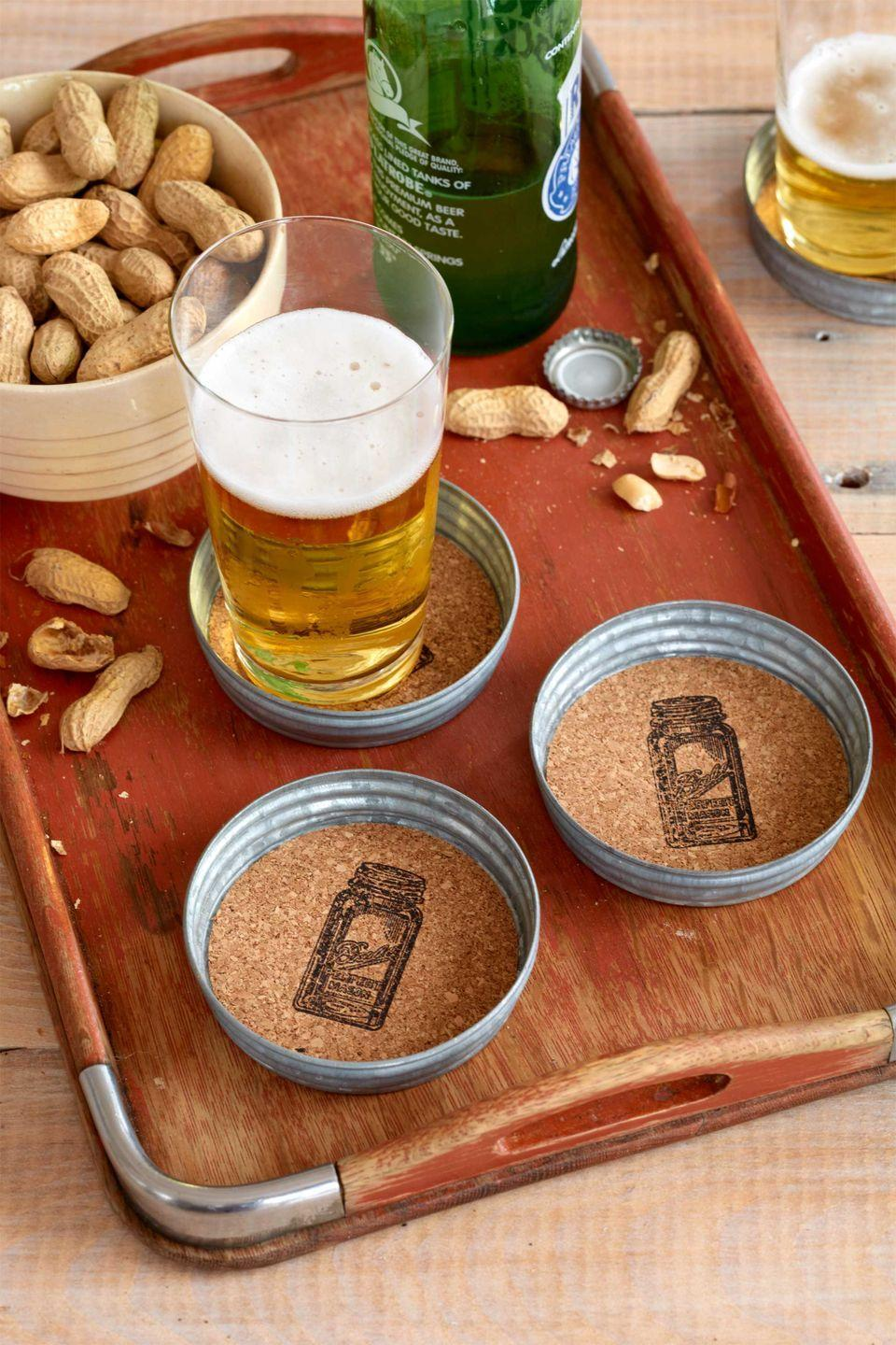 """<p>Give Dad a stylish-looking spot to rest his beer bottle while he watches the big game.</p><p><strong>Step 1:</strong> First, gather four lids: We used weathered zinc ones.</p><p><strong>Step 2:</strong> Place your lids upside down on top of <a href=""""https://www.amazon.com/Tact-Natural-04F-C6421-06AZ-Self-Adhesive-Drawer/dp/B000WEPD6U/?tag=syn-yahoo-20&ascsubtag=%5Bartid%7C10050.g.1171%5Bsrc%7Cyahoo-us"""" rel=""""nofollow noopener"""" target=""""_blank"""" data-ylk=""""slk:adhesive cork shelf liner"""" class=""""link rapid-noclick-resp"""">adhesive cork shelf liner</a><em>.</em> Trace around the lids with a pen, then cut out the circles.</p><p><strong>Step 3:</strong> Stamp an image into the center of each cork circle—ours references the classic Ball jar—using solvent-based ink, which won't smear when wet<em>. </em></p><p><strong>Step 4:</strong> Let the ink dry at least one minute, then peel the backing off the cork circles, and affix within the lids.</p><p><a class=""""link rapid-noclick-resp"""" href=""""https://www.amazon.com/KooK-Mason-Regular-Secure-Silver/dp/B079F511CS/?tag=syn-yahoo-20&ascsubtag=%5Bartid%7C10050.g.1171%5Bsrc%7Cyahoo-us"""" rel=""""nofollow noopener"""" target=""""_blank"""" data-ylk=""""slk:SHOP METAL LIDS"""">SHOP METAL LIDS</a></p>"""