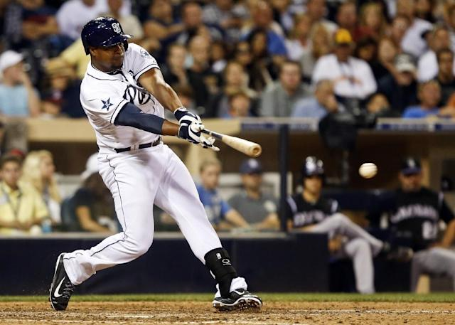 San Diego Padres' Chris Nelson drives a base hit to left field to drive in two runs against the Colorado Rockies in the eighth inning of a baseball game Tuesday, Aug. 12, 2014, in San Diego. (AP Photo/Lenny Ignelzi)