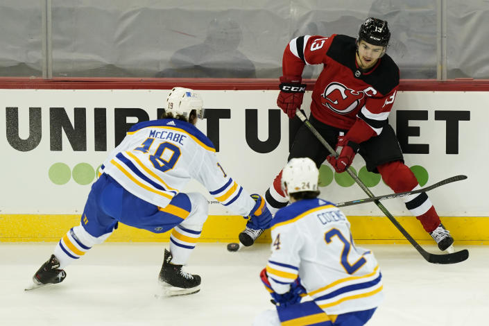 New Jersey Devils center Nico Hischier (13) battles for the puck with Buffalo Sabres defenseman Jake McCabe (19) during the first period of an NHL hockey game, Saturday, Feb. 20, 2021, in Newark, N.J. (AP Photo/John Minchillo)