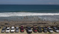Tourists' cars are parked along Los Angeles beach after it recently reopened following a lockdown to contain the spread of COVID-19 in La Guaira, Venezuela, Friday, Oct. 23, 2020. Strict quarantine restrictions forced the closure of beaches across the country in March and reopened this week. (AP Photo/Matias Delacroix)
