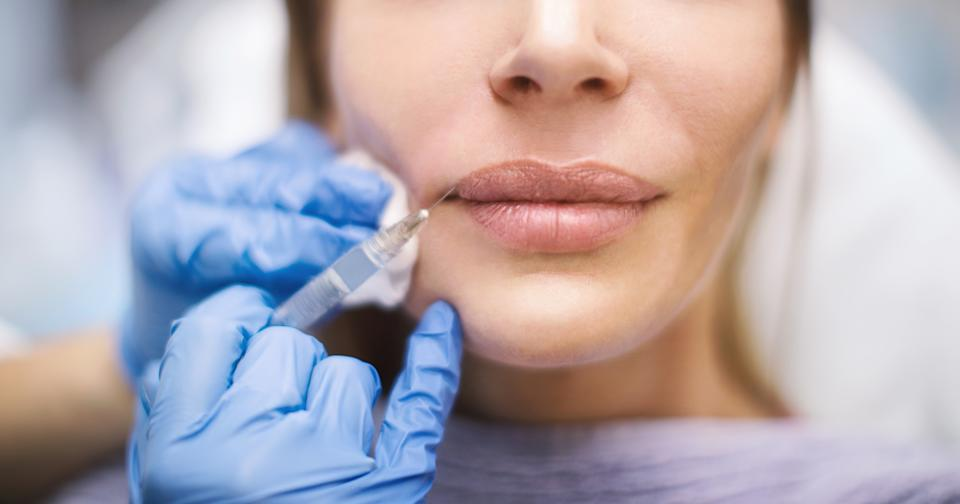 Unrecognizable woman having her lips enlarged at private medical clinic.
