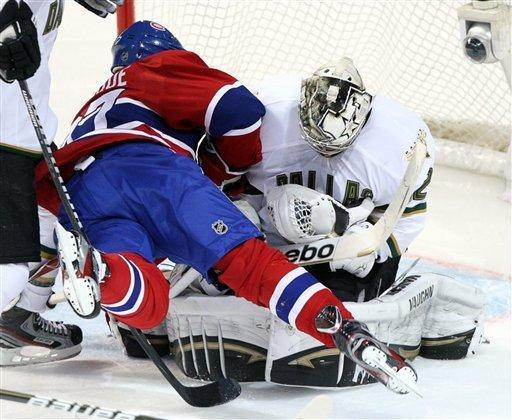 Montreal Canadiens left wing Rene Bourque (27) runs into Dallas Stars goalie Kari Lehtonen (32) during the second period of an NHL hockey game, Tuesday, Feb. 21, 2012, in Montreal. (AP Photo/The Canadian Press, Ryan Remiorz)