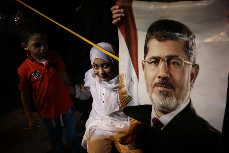 """An Egyptian child stands next to poster of the Egypt's ousted President Mohammed Morsi outside Rabaah al-Adawiya mosque, where supporters have installed a camp and hold daily rallies at Nasr City, in Cairo, Egypt, Wednesday, July 31, 2013. Egypt's military-backed government has ordered the police to break up the sit-in protests by supporters of ousted President Mohammed Morsi, saying they pose an """"unacceptable threat"""" to national security. Information Minister Dorreya Sharaf el-Din said in a televised statement Wednesday that the police are to end the demonstrations """"within the law and the constitution."""" (AP Photo/Hassan Ammar)"""