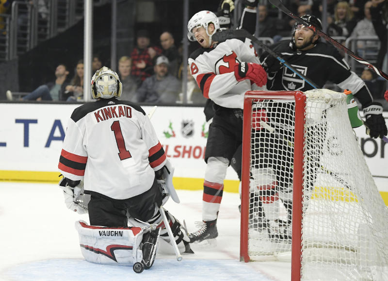 New Jersey Devils defenseman Damon Severson, center, is hit on the face by the stick of Los Angeles Kings center Michael Amadio, right, after goaltender Keith Kinkaid, left, gave up a goal to Kyle Clifford during the second period of an NHL hockey game Thursday, Dec. 6, 2018, in Los Angeles. (AP Photo/Mark J. Terrill)