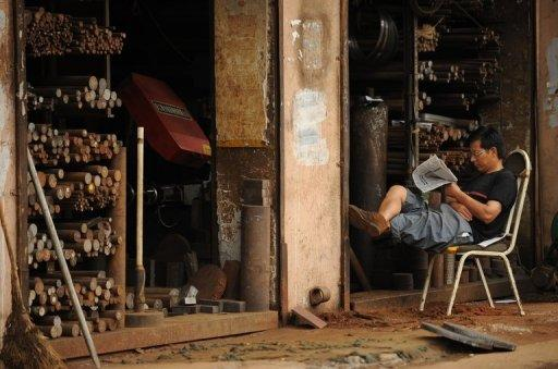 A machinist sits outside his workshop in Shanghai. Weak economic data in the current third quarter have raised fears China's growth may have slowed for a seventh straight quarter when GDP figures are released next month