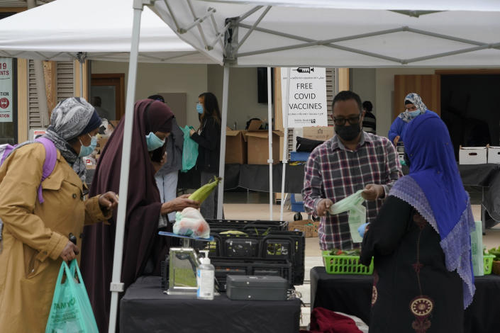 A sign for a King County (Wash.) Public Health COVID-19 vaccination clinic located at the Tukwila Village Farmers Market — which features produce grown locally by members of immigrant and refugee communities — is shown as people shop, Wednesday, Sept. 22, 2021, in Tukwila, Wash., south of Seattle. The clinic will be at the market weekly through at least most of October. (AP Photo/Ted S. Warren)