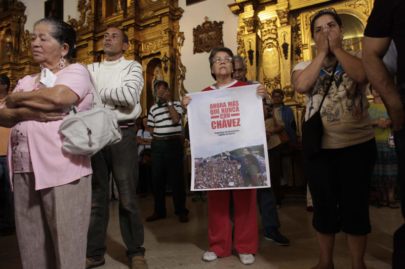 """People, one of them holding an image of Venezuela's President Hugo Chavez That reads in Spanish """"Now more than ever with Chavez,"""" gather to pray for him at a church in Caracas, Venezuela, Monday, Dec. 31, 2012. Venezuela's President Hugo Chavez is confronting """"new complications"""" due to a respiratory infection nearly three weeks after undergoing cancer surgery, his Vice President Nicolas Maduro said Sunday evening in Cuba as he visited the ailing leader for the first time since his operation. (AP Photo/Ariana Cubillos)"""