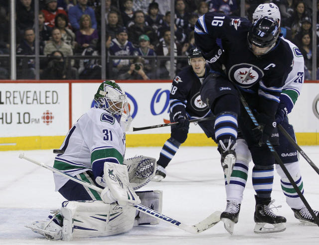 Vancouver Canucks goaltender Eddie Lack (31) saves the deflection by Winnipeg Jets' Andrew Ladd (16) during the second period of an NHL hockey game in Winnipeg, Manitoba, on Friday, Jan. 31, 2014. (AP Photo/The Canadian Press, John Woods)
