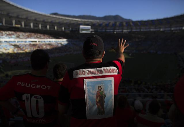 In this April 6, 2014 photo, a fan of the Flamengo soccer team wears a jersey decorated with an image of the Catholic Saint Judas Tadeu at the first match of the Rio championship at Maracana stadium in Rio de Janeiro, Brazil. Brazil's national team is seeking a record sixth World Cup title at this year's World Cup. (AP Photo/Leo Correa)