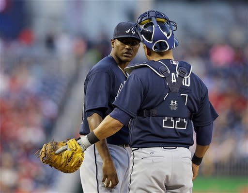 Atlanta Braves starting pitcher Julio Teheran, left, talks with catcher Gerald Laird during the first inning of a baseball game against the Washington Nationals at Nationals Park, Friday, April 12, 2013, in Washington. (AP Photo/Alex Brandon)