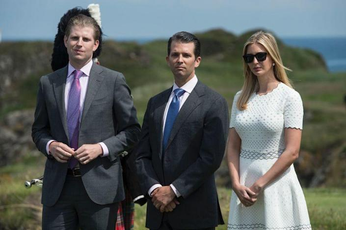 """The brothers Trump, Eric, left, and Donald Jr., who run the Trump Organization, are shown in 2016 with their sister Ivanka at the opening of a Trump resort in Turnberry, Scotland. <span class=""""copyright"""">(Oli Scarff / AFP/Getty Images)</span>"""