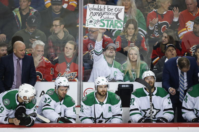 Dallas Stars fans hold up a sign behind the Stars' bench during the third period of the team's NHL hockey game against the Calgary Flames on Wednesday, Nov. 13, 2019, in Calgary, Alberta. (Jeff McIntosh/The Canadian Press via AP)
