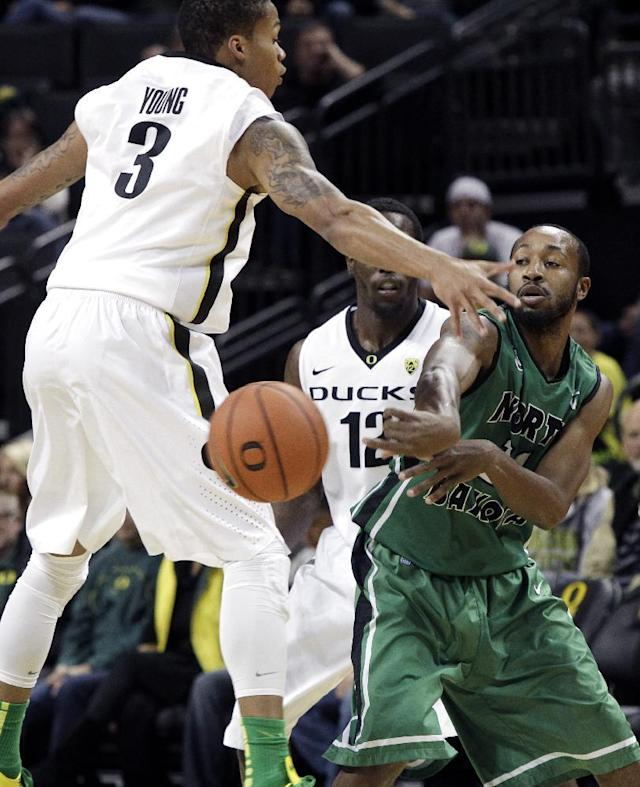 North Dakota guard Jamal Webb, right, passes off as Oregon's Joseph Young, left, and Jason Calliste double-team him at midcourt during the first half of an NCAA college basketball game in Eugene, Ore., Saturday, Nov. 30, 2013. (AP Photo/Don Ryan)