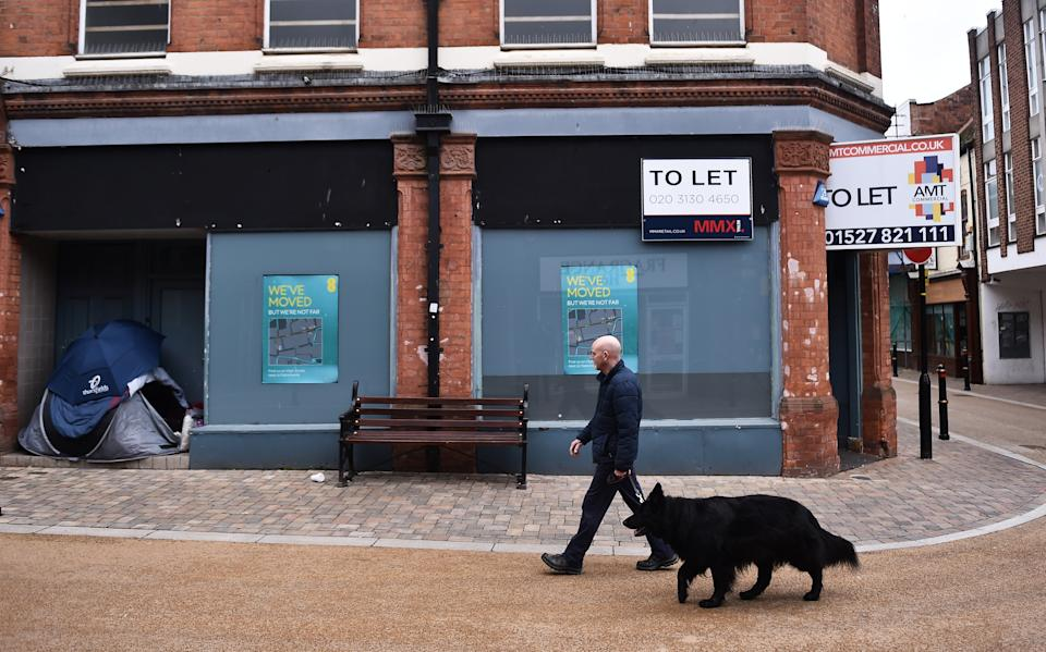 WORCESTER-ENGLAND - MARCH 27: A man walks a dog past a closed shop which is To Let in Worcester Town Center on March 27, 2021 in Worcester, England . (Photo by Nathan Stirk/Getty Images)