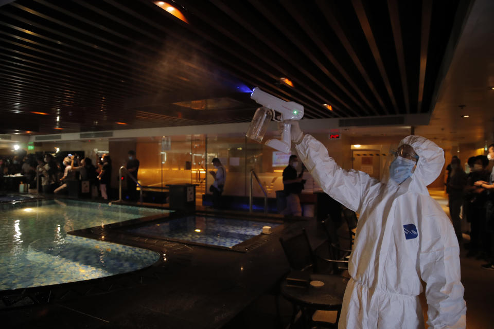 A staff member wearing protective suit sprays disinfectant on the spa facilities to help prevent the spread of COVID-19 as the massage parlor will be reopened, in Hong Kong, Thursday, Sept. 17, 2020. Government officials said that it would further relax social-distancing measures, allowing bars, amusement parks and swimming pools to re-open. (AP Photo/Kin Cheung)