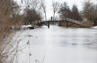 A woman crosses a bridge spanning a frozen river near Abcoude, Netherlands, Tuesday, Feb. 9, 2021. With freezing temperatures forecast for more than a week in the Netherlands, ice fever is sweeping the nation, offering a welcome respite from grim coronavirus news while also creating a challenge for authorities trying to uphold social distancing measures. (AP Photo/Peter Dejong)