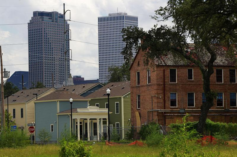 An abandoned part of the old Lafitte housing projects, right, is seen near new public assisted housing that replaces it, with the downtown skyline in background in New Orleans, Thursday, Aug. 23, 2012. The face of New Orleans is changing: Seven years after Hurricane Katrina the city many said would not recover is racially more diverse, and whiter, younger and richer; indicators not of failure but its success at reinventing itself. In fact, the city is experiencing a boom, and even gentrifying.(AP Photo/Gerald Herbert)