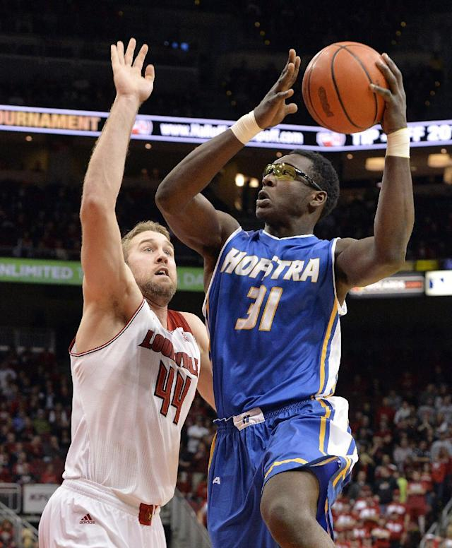 Hofstra's Moussa Kone, right, gets a shot off over the defense of Louisville's Stephan Van Treese during the first half of an NCAA college basketball game Tuesday, Nov. 12, 2013, in Louisville, Ky. (AP Photo/Timothy D. Easley)