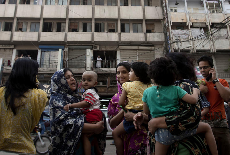 People evacuate buildings and gather on road as tremor of an earthquake was felt in Karachi, Pakistan, Tuesday, April 16, 2013. A major earthquake described as the strongest to hit Iran in more than half a century flatted homes and offices Tuesday near Iran's border with Pakistan, killing at least tens of people in the sparsely populated region and swaying buildings as far away as New Delhi and the skyscrapers in Dubai and Bahrain. (AP Photo/Shakil Adil)