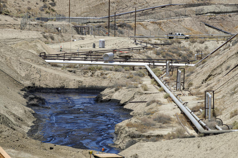 FILE - In this July 24, 2019, file photo, a crew works on seepage of 800,000 gallons of oil and brine water oil from an abandoned well in Chevron Corp's Cymric oilfield in McKittrick, Calif. Gov. Gavin Newsom's administration has temporarily banned new oil wells in California if they use an extraction method that is linked to an ongoing oil spill in Kern County. On Tuesday, Nov. 19, 2019, the Division of Oil, Gas and Geothermal Resources announced it will not approve new oil wells that use high-pressure steam to soften the thick crude underground so it can flow more easily. (Irfan Khan/Los Angeles Times via AP, Pool, File)