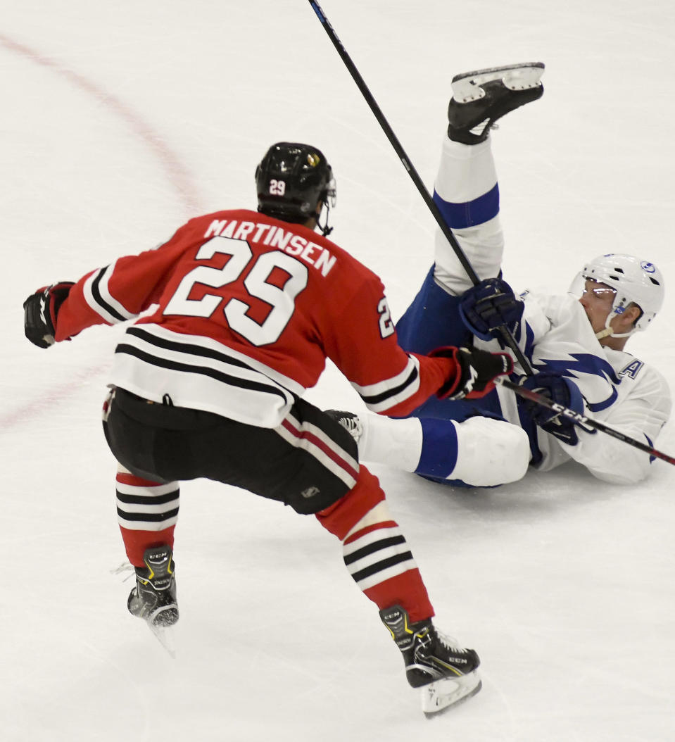 Chicago Blackhawks left wing Andreas Martinsen (29) and Tampa Bay Lightning defenseman Anton Stralman (6) fight for the puck during the second period of an NHL hockey game on Sunday Oct. 21, 2018, in Chicago. (AP Photo/Matt Marton)