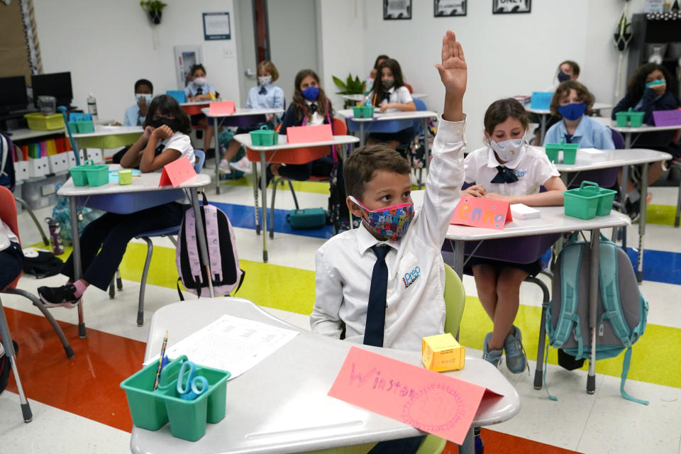 Student Winston Wallace, 9, raises his hand in class at iPrep Academy on the first day of school, Monday, Aug. 23, 2021, in Miami. Schools in Miami-Dade County opened Monday with a strict mask mandate to guard against coronavirus infections. (AP Photo/Lynne Sladky)