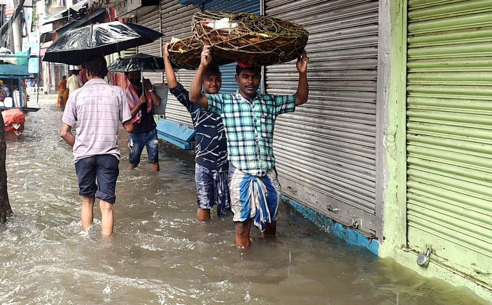 """<div class=""""paragraphs""""><p>Vendors in Kolkata wade through inundated streets after heavy downpour.</p></div>"""