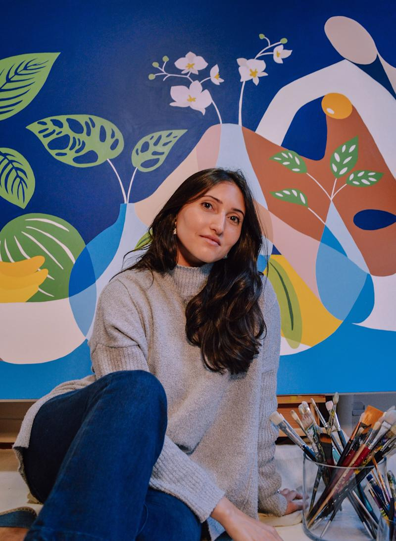 Natalia Juncadella seated in front of her vibrant painting Florecer.