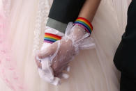 Lesbian couples Chen Ying-hsuan, right, holds Li Li-chen's hand during a military mass weddings ceremony in Taoyuan city, northern Taiwan, Friday, Oct. 30, 2020. Two lesbian couples tied the knot in a mass ceremony held by Taiwan's military on Friday in a historic step for the island. Taiwan is the only place in Asia to have legalized gay marriage, passing legislation in this regard in May 2019. (AP Photo/Chiang Ying-ying)