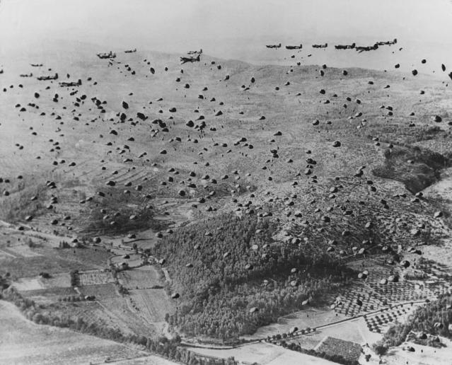 <p>Hundreds of American paratroopers drop into Normandy, France, on or near D-Day, June 6, 1944. Their landing, part of an all-out Allied assault from air and sea, was the beginning of a sweep through Europe that would finally defeat Nazi Germany. (Photo: Hulton-Deutsch Collection/Corbis via Getty Images) </p>