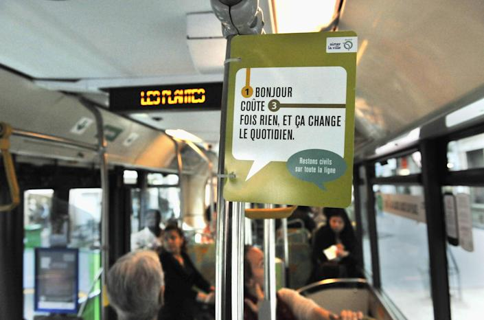 """This Sept. 21, 2011 photo provided by Paris subway operator RATP, shows a campaign poster in a Paris bus. France, a country famed for its arrogant waiters and proud taxi drivers, is finally getting fed up with rudeness. Polling trends show that impoliteness is now topping lists on causes of stress for the French, who lament that people don't say """"thank you"""" anymore. Paris public transport is weighing in, with a summer-long publicity campaign poking fun at gallic incivility. Poster reads: A Bonjour, doesn't cost a thing."""" (AP Photo/Bruno Marguerite, RATP)"""
